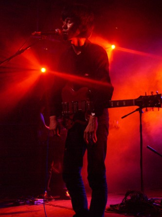 Hands drooping, a musician sings in red light