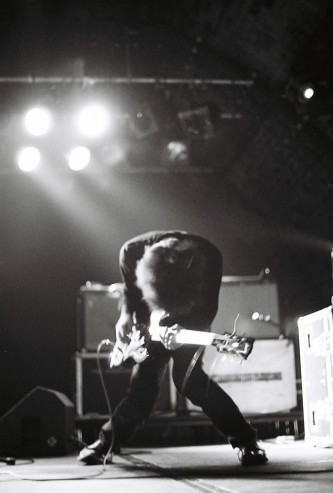 Hunched over guitar player lit from behind, amplifiers visible in background