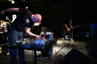 a guitarist and a bald man perform noise music in bright lights