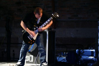 Guitar player in front of a large amplifier