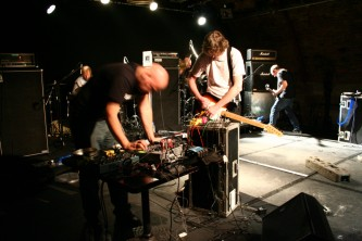 Four men on a stage manipulating instruments and feedback