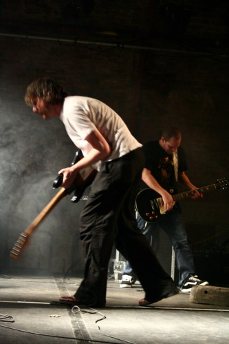 Two men playing guitars in opposite directions