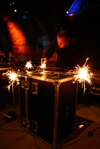 A man with a small beard burns sparklers indoors on a table