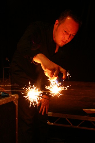 A man's hand reaches forward to light more fireworks, his face is orange