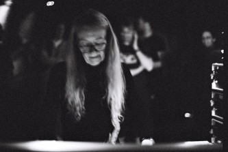 A woman wearing glasses looks down at a mixing console