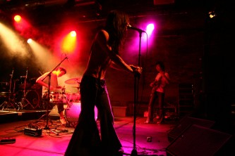 Flared trousers in the foreground, rock trio in pink light
