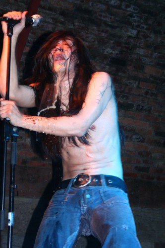 A half naked man producing liquids from many orifices holds a microphone