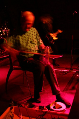 Tony Conrad bowing a torn drum head, Keiji Haino in the background