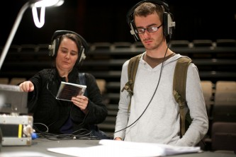 Two people wear headphones in a well lit space