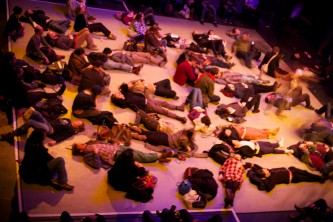 audience members are scattered lying on a floor, taken from above