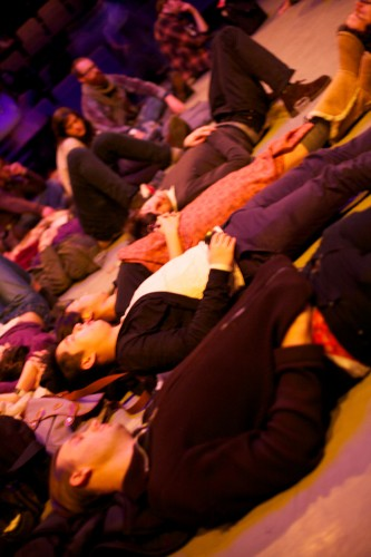 audience members are scattered lying on a floor, taken from an angle