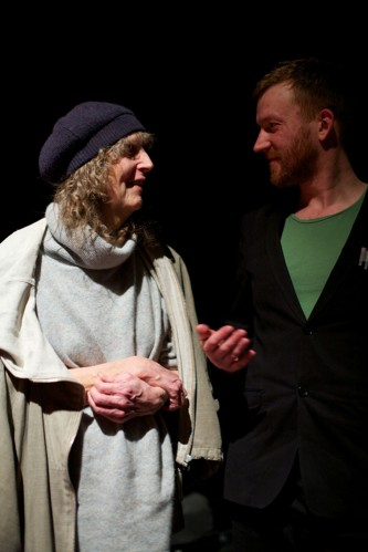 Catherine Christer Hennix with long hair, a hat speaks to Barry Esson in a suit