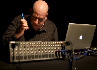 A man with a bald head uses a torch to look at a mixer next to a laptop