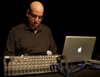 A man with a bald head looks at a mixer next to a laptop