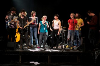 A cover band comprising many people rehearse live