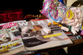 A close up of 2 magazine covers with flump sweets strewn across them
