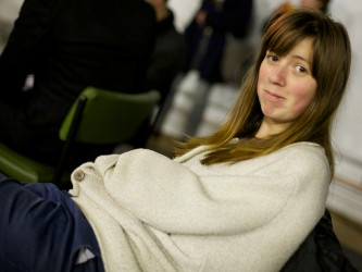 A woman in a beige jumper and long hair looks at the camera and smiles