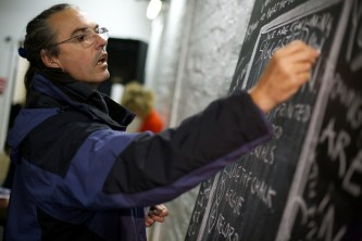a man in glasses and a jacket stretches to write on a vertical blackboard