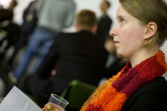 A woman in a orange scarf looks up at someone out of frame