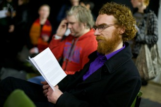 A man with a beard sits and reads a handout