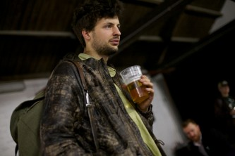 A man looks out of frame as he holds a pint of beer