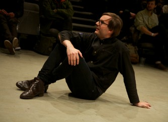Mattin dressed in black sits on the floor hugging his knees with one arm
