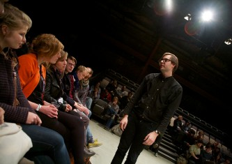 Mattin dressed in black approaches and looks at audiences sat in a seating bank