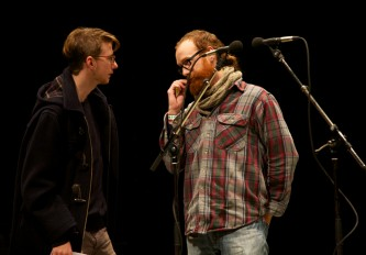 A man fiddles with his beard as he talks to another audience member by a mic