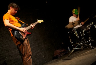 A guitarist in an orange t-shirt plays with a drummer in a baseball cap