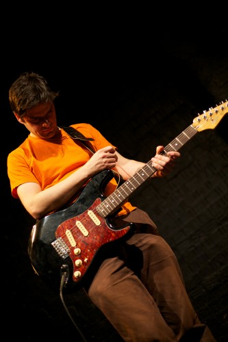 A man in an orange t-shirt looks down as he plays a maroon guitar