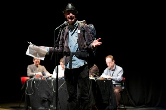A man with a rucsac and hat reads into a microphone