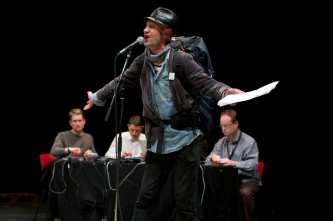 A man spreads his arms for emphasis while three performers work behind him