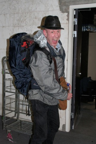 Tam Dean Burn in hat, outdoor coat and rucksack pulls a very excited face