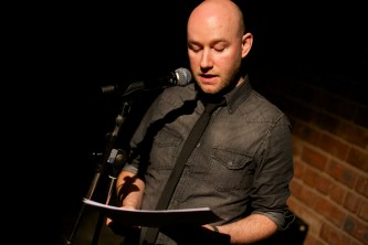 A man with a shaved head in a dark shirt reads into a microphone