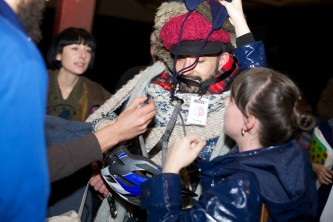 Hands of audience members place more hats and scarfs onto Stephen Anderson