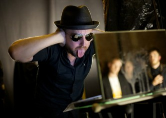 Tim Goldie wearing hat and sunglasses covers his ears and puts his tongue out