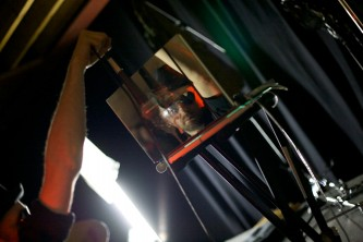 A reflection in a mirrored laptop of Tim Goldie swinging a microphone
