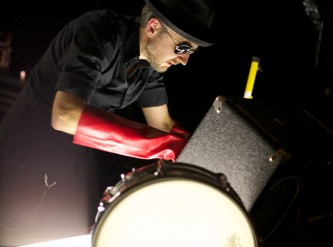 Tim Goldie wearing a red rubber glove, hat and sunglasses looks in an amp case