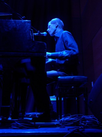A man playing a piano in blue light