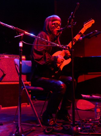 Keiji Haino seated, singing into a microphone while playing a guitar