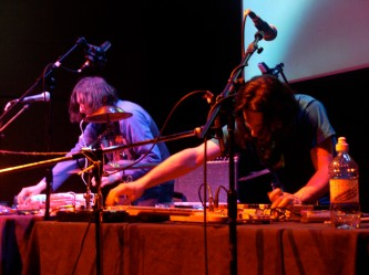 Two men playing with electronic equipment and microphones
