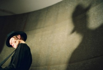 Jandek wearing a hat casting a Nosferatu vibe shadow on a curved wall