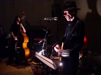 A skeletal Jandek playing a guitar with acoustic bass in the background