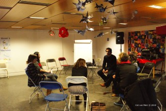 Paper birds hanging from the ceiling, Loic talking with participants