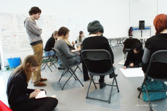 Taku Unami writing on a piece of paper on the floor surrounded by seated people