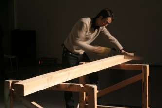 Christof Migone saws a large piece of wood