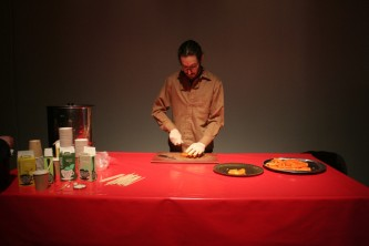 Jarrod Fowler cuts carrots on a red table