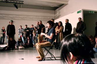 Marc Baron plays saxophone sat on a chair, an audience around
