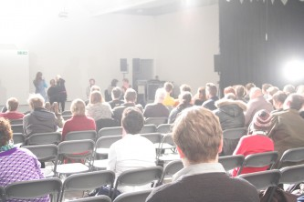 A back shot of a brightly lit audience