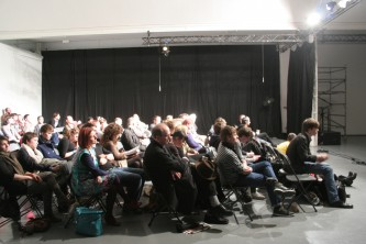 A side shot of a brightly lit audience